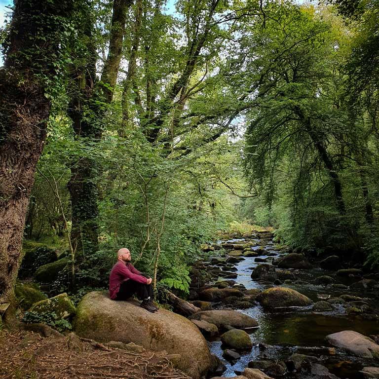 On voit le Druide Taliesin en séance de sylvareliance. Il est assis au bord d'une rivière en train de prendre un bain de forêt.