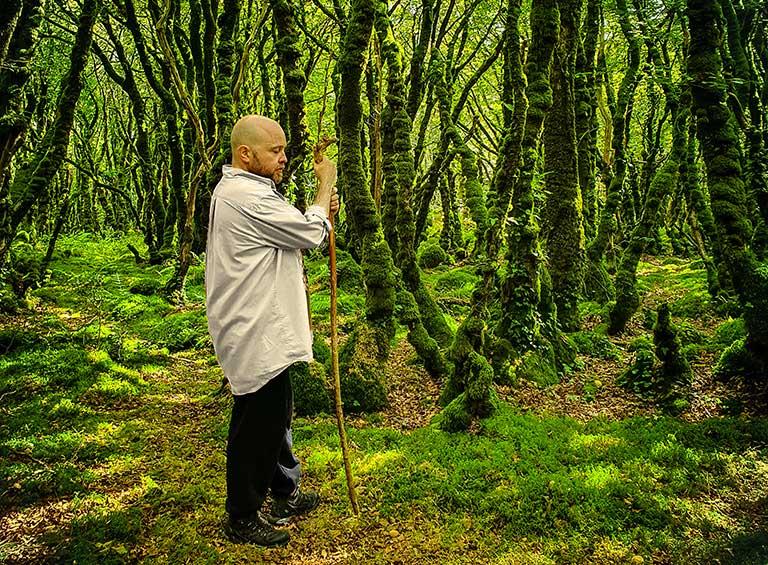 Un prêtre de Cernunnos, druide, dans une forêt moussue et verte, se tient debout appuyé sur son bâton.